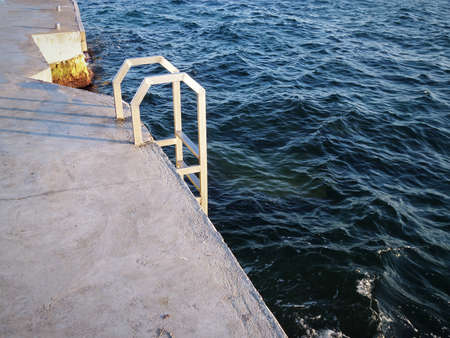 Ladder made of stainless steel into the water. Caspian Sea. Stock Photo