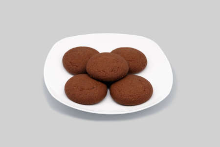 Oatmeal cookies on a white plate. Close-up. Isolated on a gray background. Stock Photo