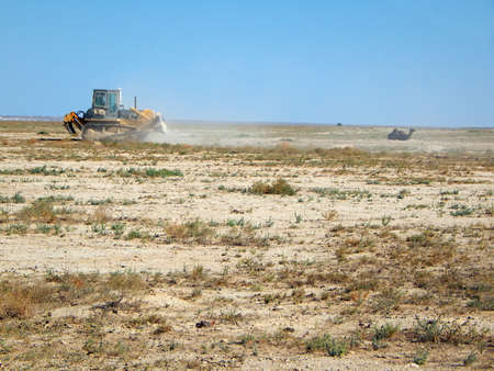 Bulldozer in the steppes level the site. Kazakhstan. Oil field. Mangistau region. August 17, 2019 year.