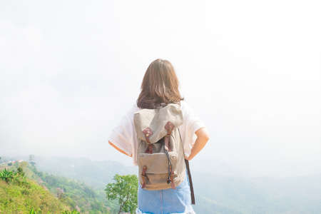 Back side of traveller girl looking at the blue sky on the top of mountain, travel and active lifestyle concept Stock Photo