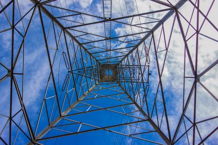 inside the electricity transmission pylon against blue sky. High voltage pylon