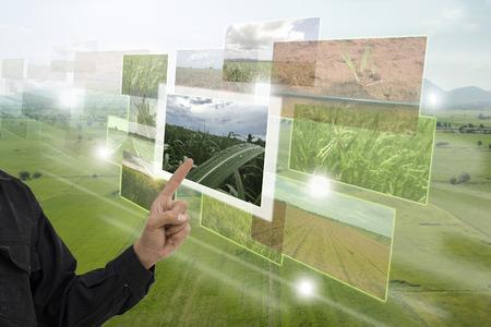 Internet van dingen (landbouwconcept), slimme landbouw, industriële landbouw. Gebruiker wijst hand om verbrede realiteitstechnologie te gebruiken om te controleren, te bewaken en te beheren in de boerderij