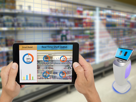 smart retail concept, A store's manager can check what data of real time insights into shelf status which report on a tablet from artificial intelligence(ai) smart robot while scanning goods and price 免版税图像