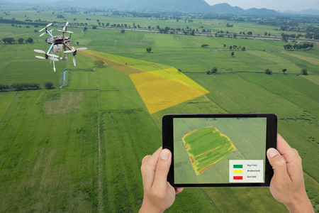 drone for agriculture, drone use for various fields like research analysis, safety,rescue, terrain scanning technology, monitoring soil hydration ,yield problem and send data to smart farmer on tablet Foto de archivo