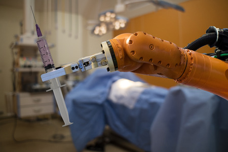 robot in medical concept, robot (artificial intelligence)hold the medical syringe in the operating room  for prepare to surgery the patient for faster recovery time, less cosmetic damage and low costs Archivio Fotografico