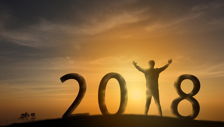 Silhouette man stand on the top of mountain and look through the sunrise, sunset and give two hand up to feel like a winner, success, finish,reach a goal of live, jobs,work with in 2018 new years Stock Photo