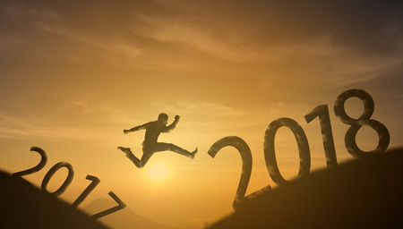brave man successful concept,silhouette man jumping over the sun between gap of the mountain from 2017 to 2018 new year , it feel like a winner, success, finish,reach a goal of live, jobs,work Banco de Imagens