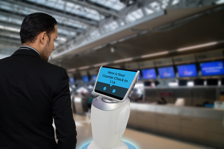 Smart robotic technology concept, The passenger follow a service robot to a counter check in in airport, the robot can help and give some information to passenger quickly Banco de Imagens