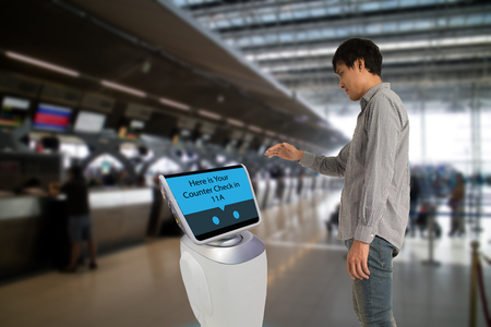 Smart robotic technology concept, The passenger follow a service robot to a counter check in in airport, the robot can help and give some information to passenger quickly Stock Photo