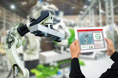 iot industry 4.0 concept,industrial engineer using software (augmented, virtual reality) in tablet to monitoring machine in real time.Smart factory use Automation robot arm in automotive manufacturing Stock Photo