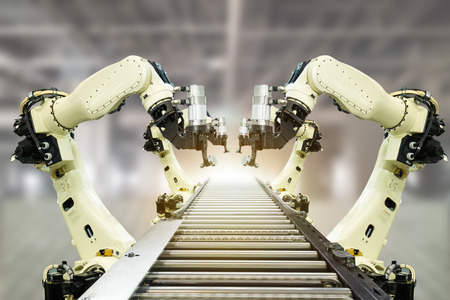 iot industry 4.0 technology concept.Smart factory using trending automation robotic arms with part on conveyor belt in operation line. Automotive manufacturing use it for precision, Repetition, intense