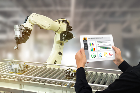 iot industry 4.0 concept,industrial engineer using software (augmented, virtual reality) in tablet to monitoring machine in real time.Smart factory use Automation robot arm in automotive manufacturing Zdjęcie Seryjne - 93721412