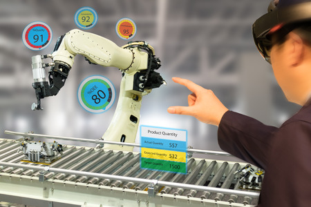 iot industry 4.0 concept,industrial engineer(blurred) using smart glasses with augmented mixed with virtual reality technology to monitoring machine in real time.Smart factory use Automation robot arm 스톡 콘텐츠