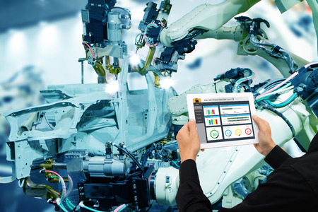 iot industry 4.0 concept,industrial engineer using software (augmented, virtual reality) in tablet to monitoring machine in real time.Smart factory use Automation robot arm in automotive manufacturing Banque d'images