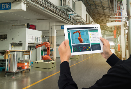 iot industry 4.0 concept,industrial engineer using software (augmented, virtual reality) in tablet to monitoring machine in real time.Smart factory use Automation robot arm in automotive manufacturing 免版税图像