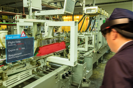 iot smart industry 4.0 concept. Industrial engineer(blurred) using smart glasses with augmented mixed virtual reality technology to see the detail of part which will expired and prepare spare parts