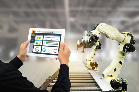 iot industry 4.0 concept,industrial engineer using software (augmented, virtual reality) in tablet to monitoring machine in real time.Smart factory use Automation robot arm in automotive manufacturing 스톡 콘텐츠