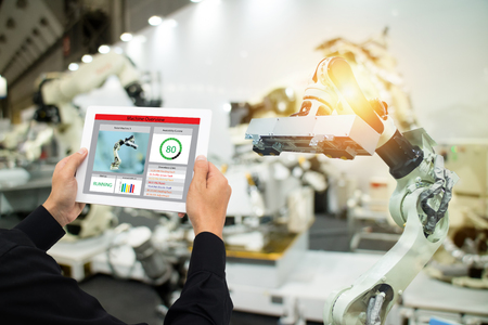 iot industry 4.0 concept,industrial engineer using software (augmented, virtual reality) in tablet to monitoring machine in real time.Smart factory use Automation robot arm in automotive manufacturing Фото со стока