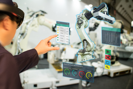 iot industry 4.0 concept,industrial engineer(blurred) using smart glasses with augmented mixed with virtual reality technology to monitoring machine in real time.Smart factory use Automation robot arm Archivio Fotografico