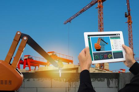 Usine intelligente iot, concept technologique de l'industrie 4.0, tablette d'utilisation par l'ingénieur pour surveiller, détecter et analyser le bras du robot pour la construction, utilisation du bras du robot pour poser un mur ou une usine de briques et de plâtre