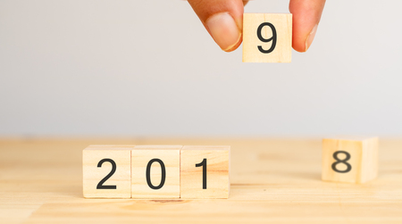 happy new year 2019 trend concept, Hand man try to replace number of year from 2018 to 2019 on the wooden table Stock Photo