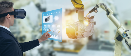 iot industry 4.0 concept,industrial engineer using smart glasses with augmented mixed with virtual reality technology to monitoring machine in real time.Smart factory use Automation robot arm