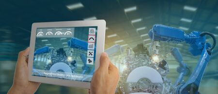iot industry 4.0 concept,industrial engineer using software (augmented, virtual reality) in tablet to monitoring machine in real time.Smart factory use Automation robot arm in automotive manufacturing 版權商用圖片