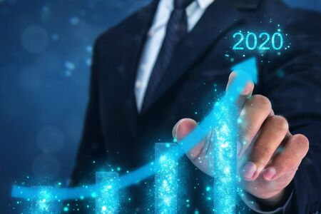 2020 concept,business man point hand on the top of arrow graph with high rate of growth in year 2020. The success and growing growth graph in the company or industrial after investment in 2020