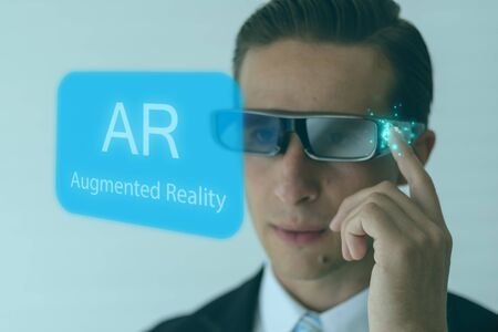 smart glasses futuristic technology concept, man wear smart glasses an augmented mixed virtual reality with artificial intelligence combine deep, machine learning, digital twin, 5G, industry 4.0 tech Фото со стока