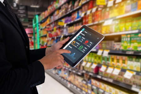 iot smart retail in the futuristic concept, the retailer hold the tablet and use augmented reality technology monitor data of out of shelve, price, planogram, campaign of compliance in the real time