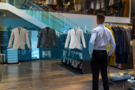 iot smart retail futuristic technology concept, happy man try to use smart display with virtual or augmented reality  in the shop or retail to choose select ,buy cloths and give a rating of products 版權商用圖片