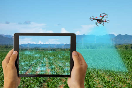 drone for agriculture, drone use for various fields like research analysis, safety,rescue, terrain scanning technology, monitoring soil hydration ,yield problem and send data to smart farmer on tablet Banco de Imagens