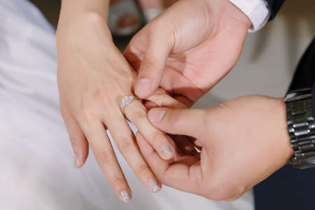 Hand of lover are wearing a ring on her wedding day