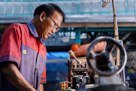 Asians Craftsman being machined steel in a factory. Stock Photo