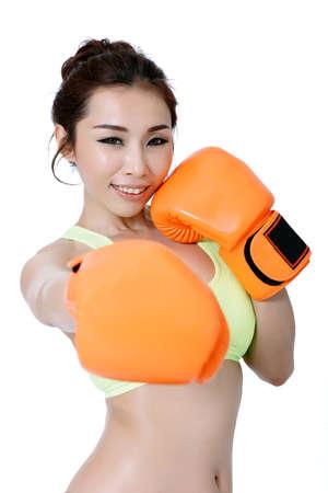 mitt: Sexy asian young women slim fit wearing orange mitt boxing on white Studio Background. Stock Photo