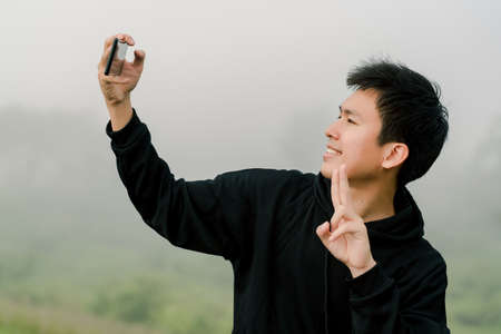 Asian boy teenager wearing black winter clothing Stand to take pictures of yourself with a mobile phone On the road along the reservoir in the morning mist And morning sunlight Happy expression