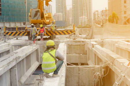 The construction worker in the green waistcoat and the yellow helmet and a black mask kneeling down on the steel beam in the construction area with yellow crane in the background. Standard-Bild
