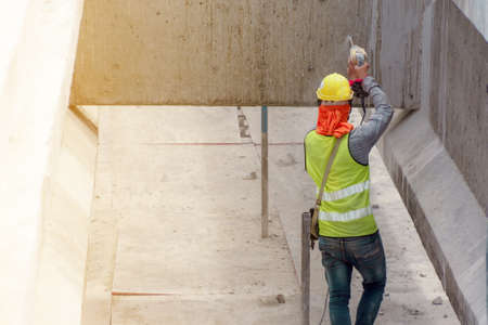 The construction worker in the green waistcoat and the yellow helmet is piercing the concrete wall in the construction area Stock Photo