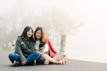 Two asian girls Very close friends Wearing a sweater, take a selfie phone, take pictures in a tourist attraction Along the road beside the reservoir in the thick fog With a smiling expression of happiness