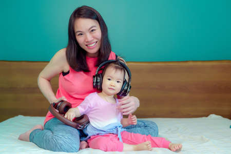 A beautiful Asian lady mother is pregnant. Take a big headset Come to the stomach Let the child in the belly listen Have a little daughter playing beside happily