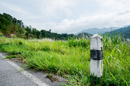 Black and white stones  concrete pillar kilometers on the road are covered with grass. With a gray sky, rocky kilometers on the road are covered with grass. With a gray sky, rocky kilometers 版權商用圖片