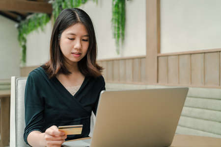 Closeup Asian beautiful woman Wearing a black shirt Sitting in the house Have a credit card in hand Is buying online products with a laptop computer.
