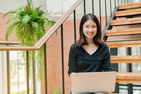 Closeup Asian beautiful woman Wearing a black shirt Sitting in the stairs in the house Use a laptop computer to work happily