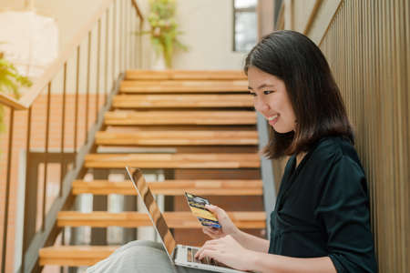 Closeup Asian beautiful woman Wearing a black shirt Sitting in the stairs in the house Have a credit card in hand Is buying online products with a laptop computer.