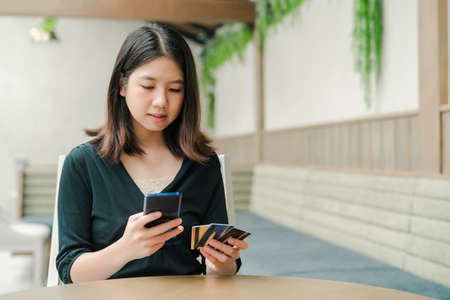 Asian beautiful woman Wearing a black shirt Sitting in the house There is a credit card in your hand and you are holding the phone. Happy face. Stock Photo