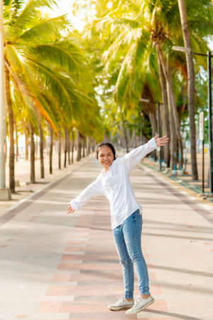 A young Asian woman wearing a white shirt and jeans is posing for a photo on the Bangsaen beach walkway on a day when there are not many people behind the coconut trees. On a clear day, Bangsaen, Thailand