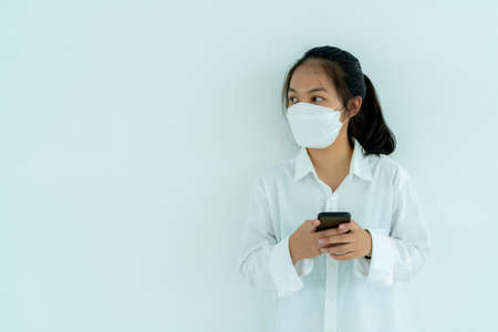 Asian teenage girl wearing white shirt Leaning against a white wall, pressing a cell phone with a medical mask covering his mouth and nose. Standard-Bild