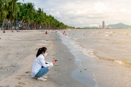 A young Asian woman in a white shirt is sitting on the beach with soft waves on a clear day.