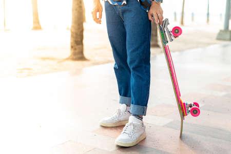 An Asian man's legs are standing. Stand holding a surf skate on the beach walkway of Bangsaen. Thailand Standard-Bild