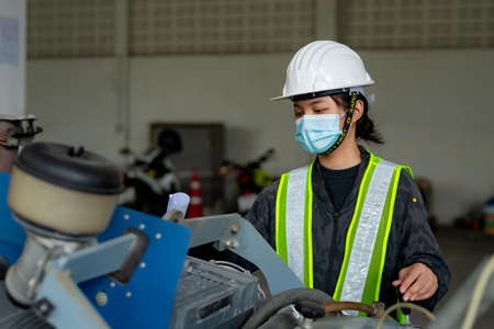 Young Asian female engineer wearing a medical mask to cover her mouth and wearing a white safety helmet Inspecting large floor cutters in the construction zone.